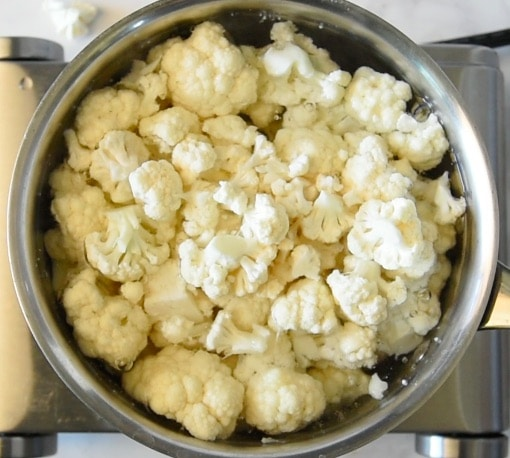 A pan of cauliflower florets boiling in a pan