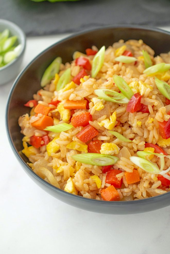 A closeup showing the rice with red peppers, egg and green onion