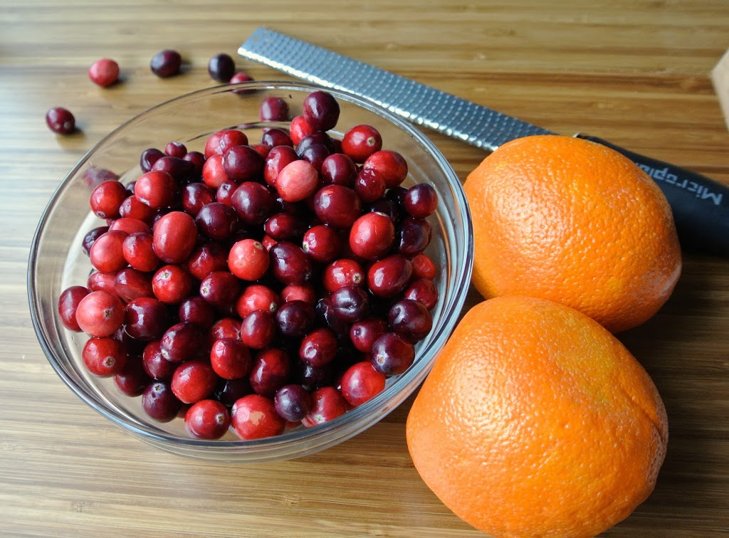 A bowl of fresh cranberries and 2 oranges ready to be made into sauce