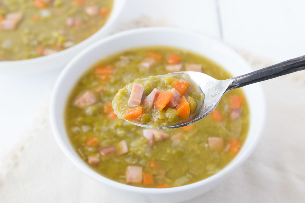 A spoonful of soup showing the ham, carrots and green peas