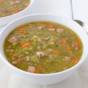Ham and split pea soup served in a white bowl with a spoon