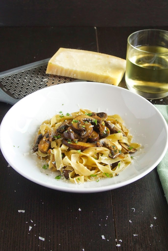 A white bowl with tagliatelle with mushrooms (Tagliatelle ai funghi) parmesan cheese and a glass of white wine