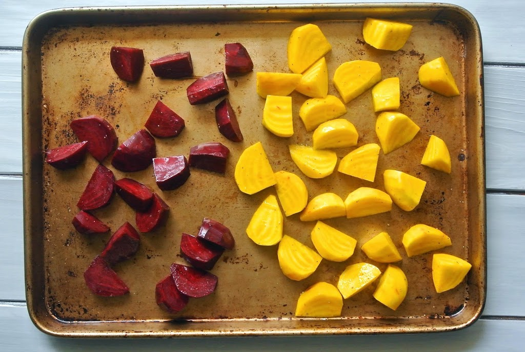 Red and gold beets on a baking sheet ready to be roasted