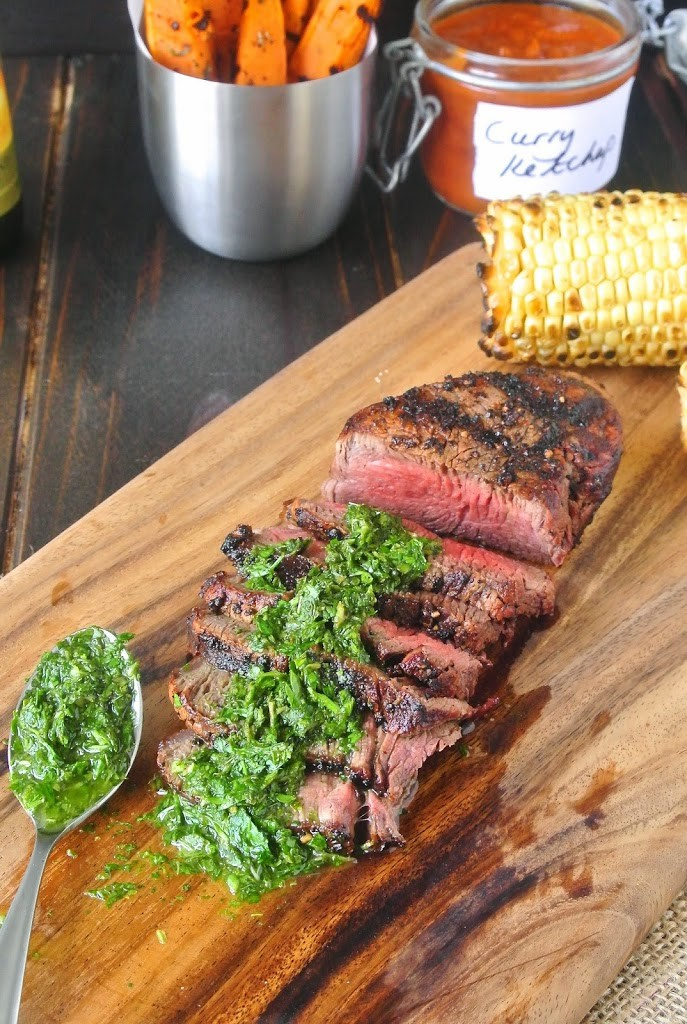 Perfectly grilled filet mignon sliced on a board with mint and parsley