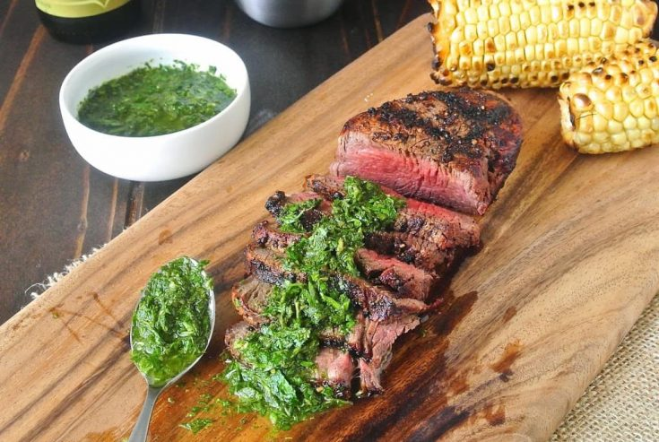 Grilled filet mignon with mint and parsley served on a cutting board with grilled corn on the cob