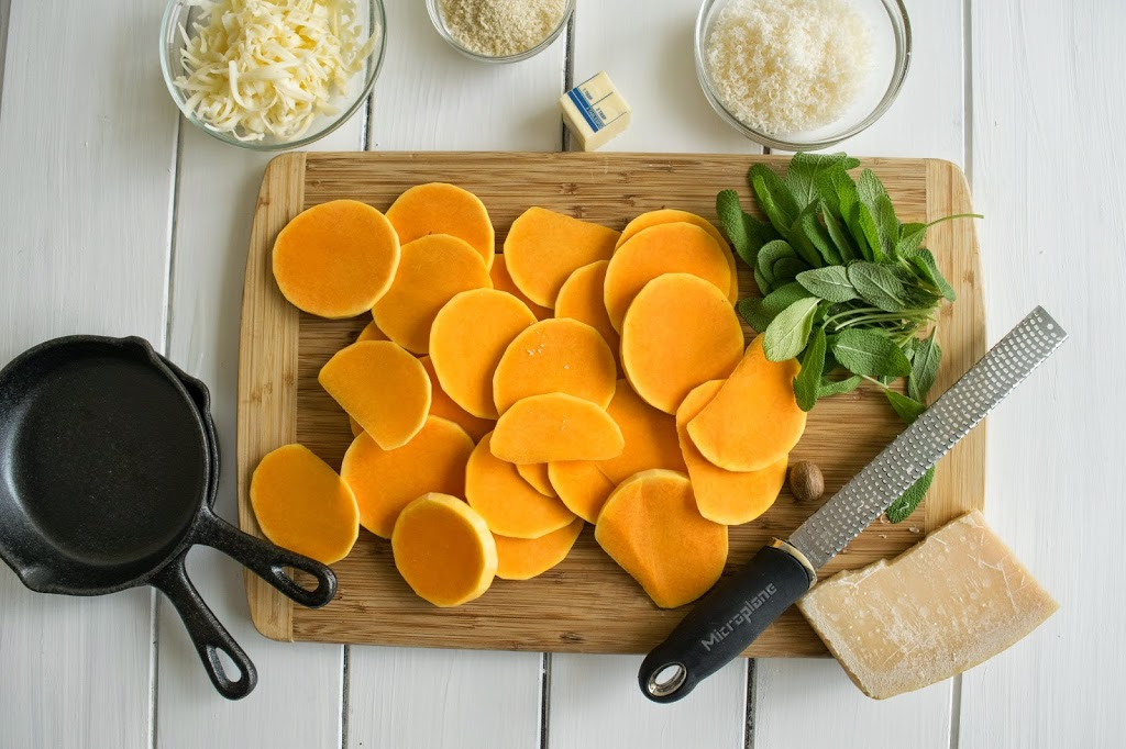 A cutting board with sliced butternut squash and cheeses