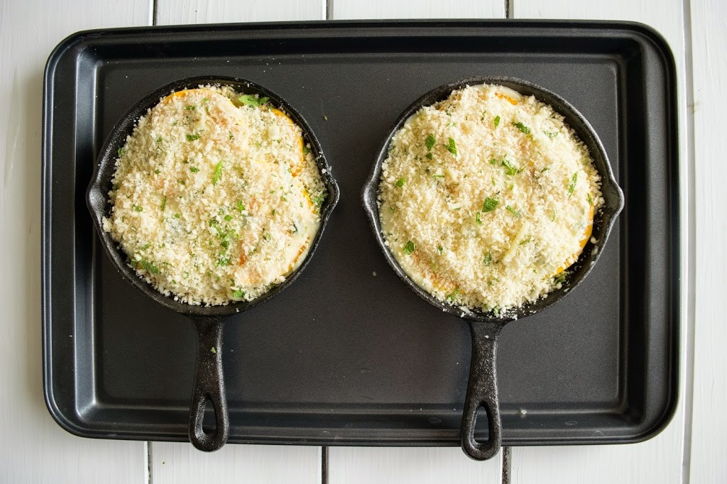2 mini cast iron skillets with butternut squash and sage gratin on a baking sheet ready for the oven