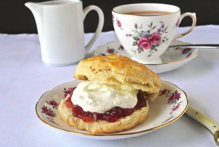 An English scone topped with clotted cream and strawberry jam and a cup of tea.