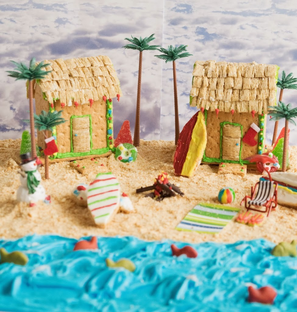 2 beach houses made out of graham crackers on a beach of graham cracker sand and blue frosting ocean