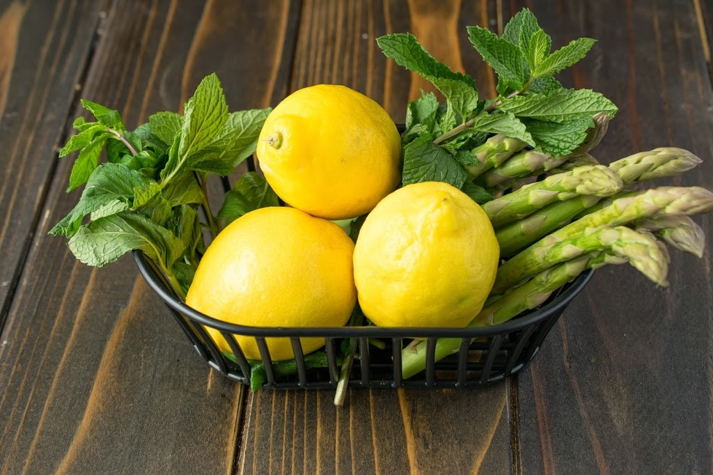 A basket of fresh lemons, fresh mint and asparagus