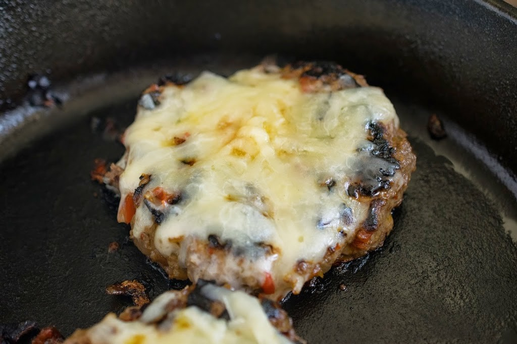 A burger cooking covered in melted cheese
