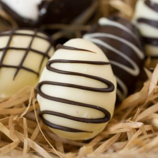 A white chocolate egg drizzled with dark chocolate