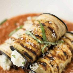 A closeup showing the grilled eggplant garnished with fresh basil