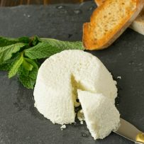 Ricotta cheese on a slate board with a knife and crusty bread
