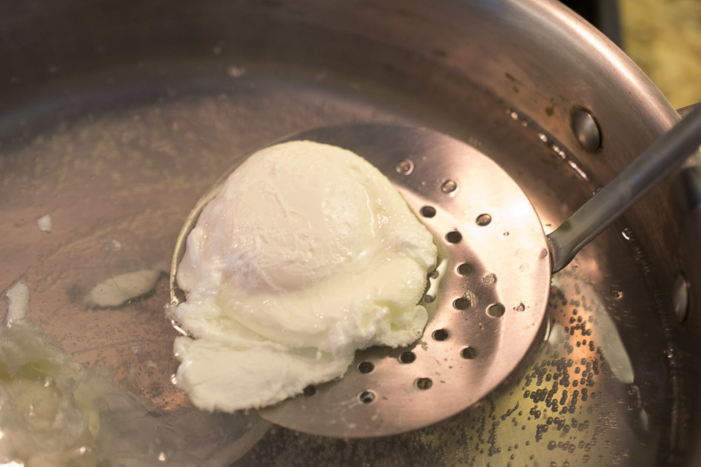 Removing a poached egg from a pan of water with a slotted spoon