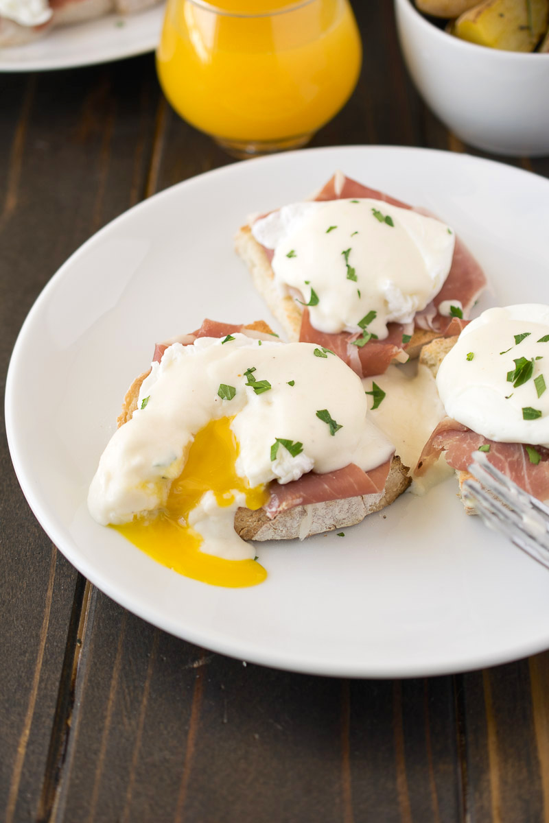 Italian eggs benedict on a white plate showing a perfectly poached egg with a runny yolk