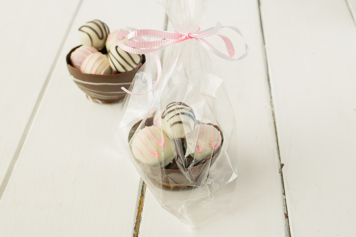 Chocolate truffles in paper cups on a white plate