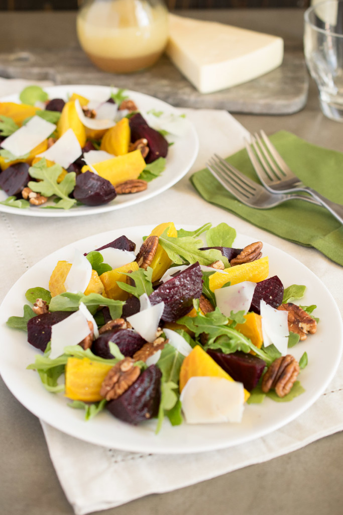 Roasted beet salad on a white plate with 2 forks