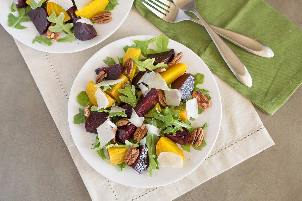 An overhead image of roasted beet salad is dressed simply with a red wine vinaigrette on a white plate with 2 forks