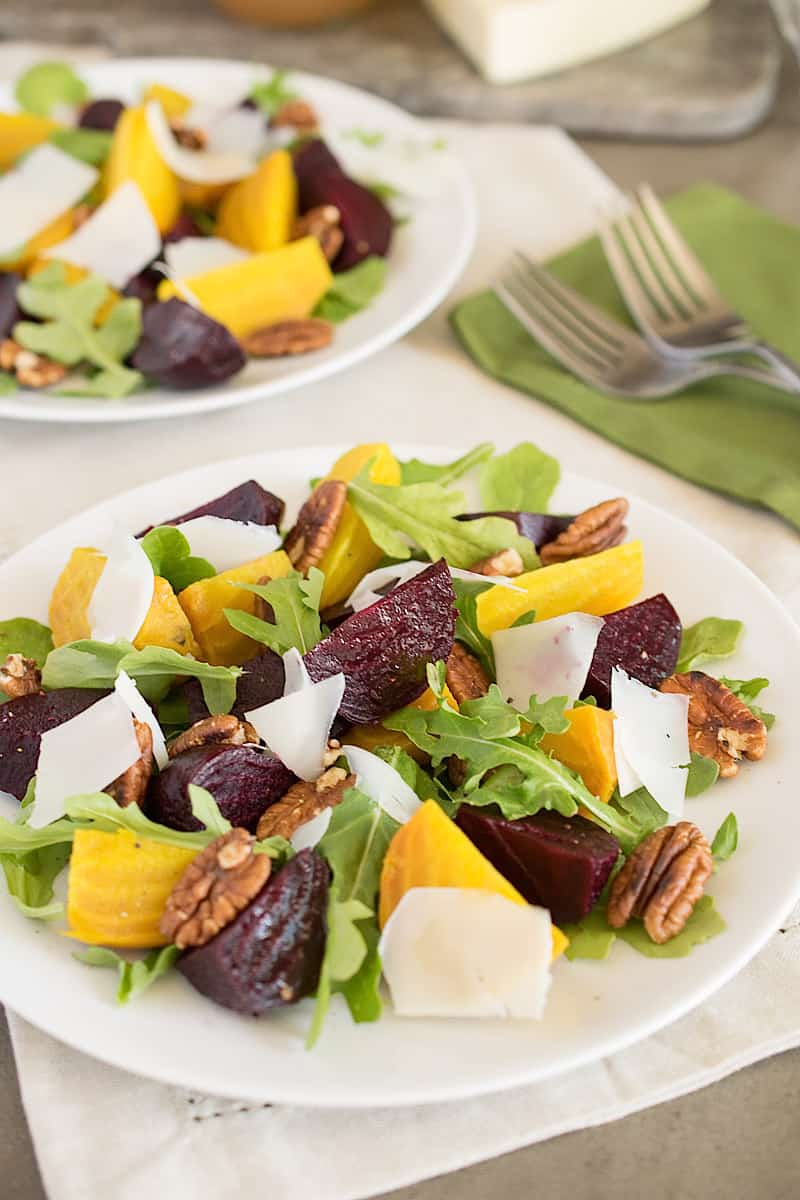 Roasted beet salad with arugula and sliced cheese on a white plate