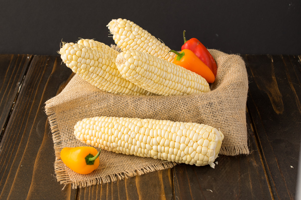 Fresh from the farmers market corn on the cob displayed with sweet mini red and yellow peppers