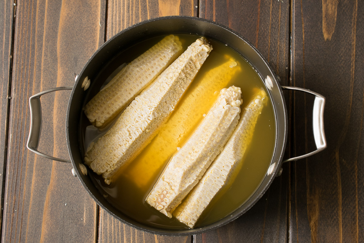 Corn kernels in a pan of water to make stock for soup