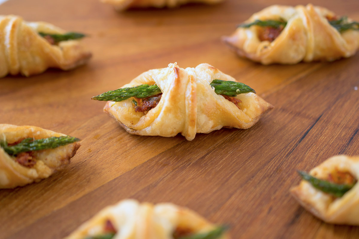 Asparagus, sun-dried tomato puff pastry bites are pretty and delicious bites. The name might be a mouthful, but they are perfect 1-biters to enjoy with friends, drinks and summer get-togethers.