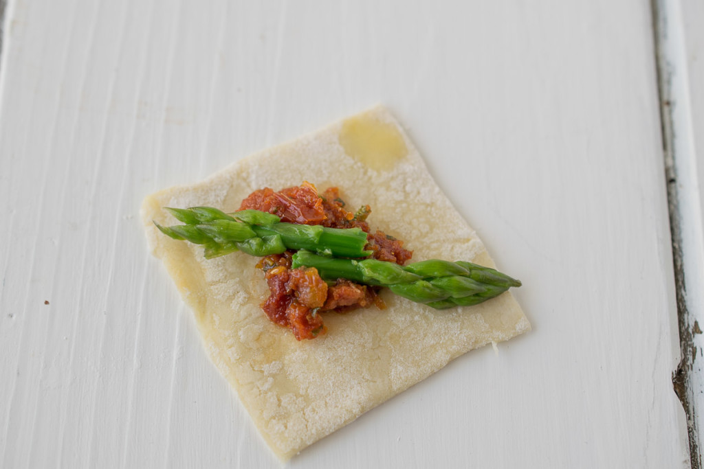 2 asparagus tips and sun-dried tomato on a square of puff pastry