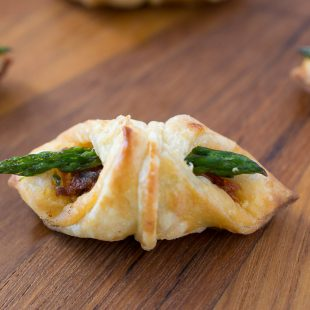 An asparagus sun-dried tomato puff pastry bite on a board