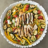 Pasta, grilled chicken and vegetables in a white bowl