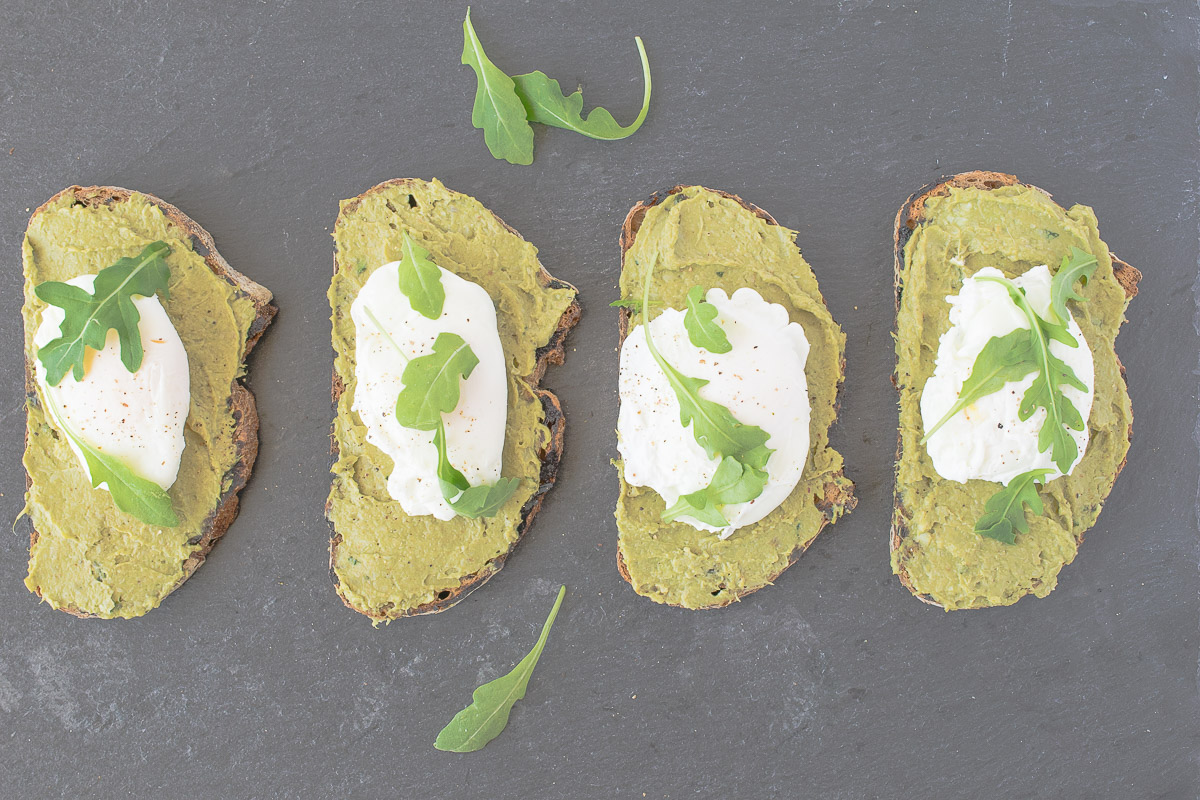 An overhead image of 4 avocado artichoke toast with poached egg garnished with arugula