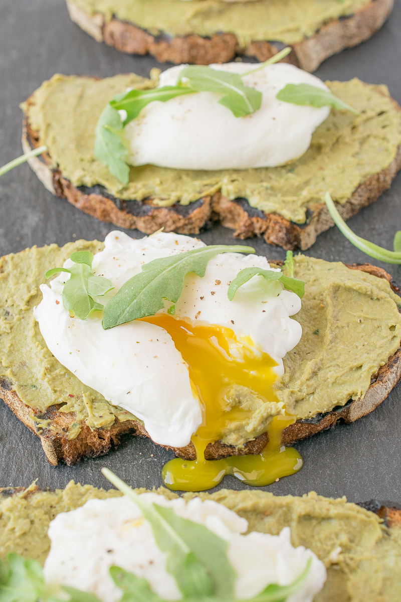 4 Avocado artichoke toast with poached eggs on a slate board