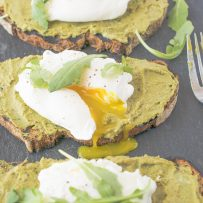 A poached egg on avocado artichoke toast cut open with yolk running out
