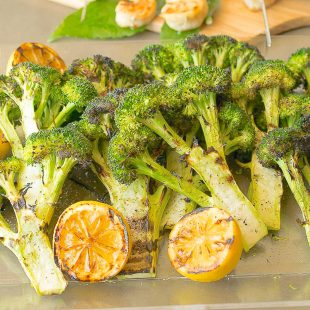 Grilled broccoli with lemon slices on a serving board