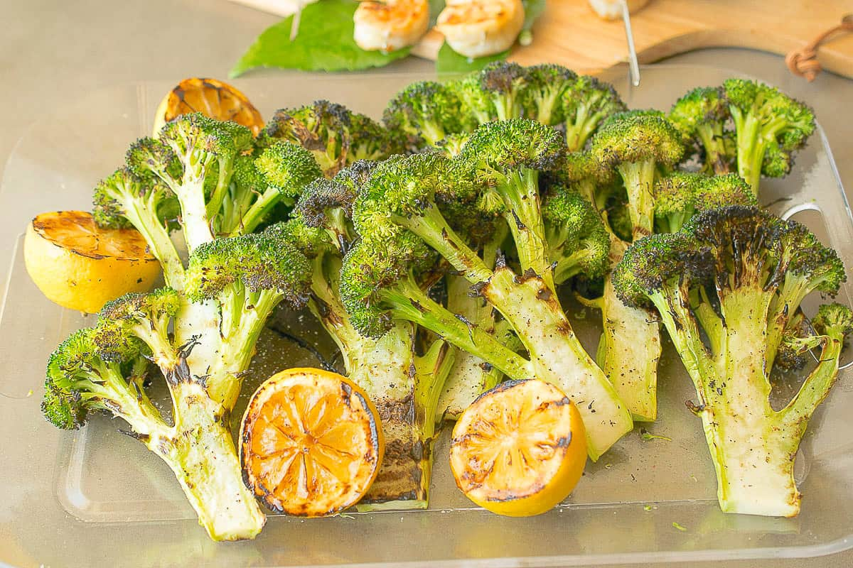 A tray of freshly grilled broccoli with grilled lemon
