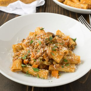 Rigatoni pasta in a white bowl mixed in a lentil vegetable sauce