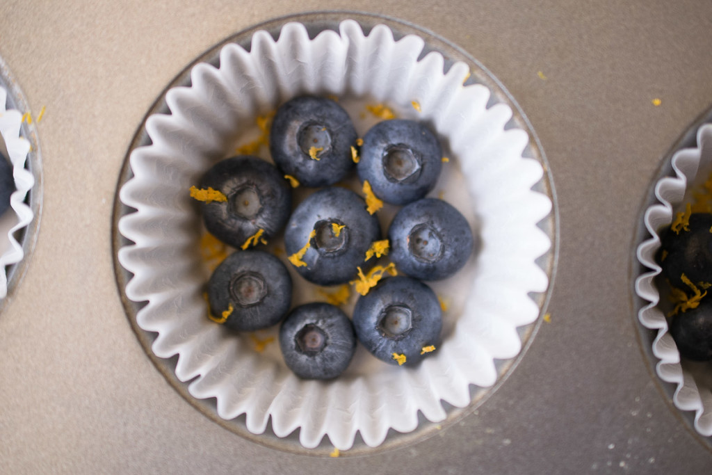 Fresh blueberries and orange zest in the bottom of a muffin cup