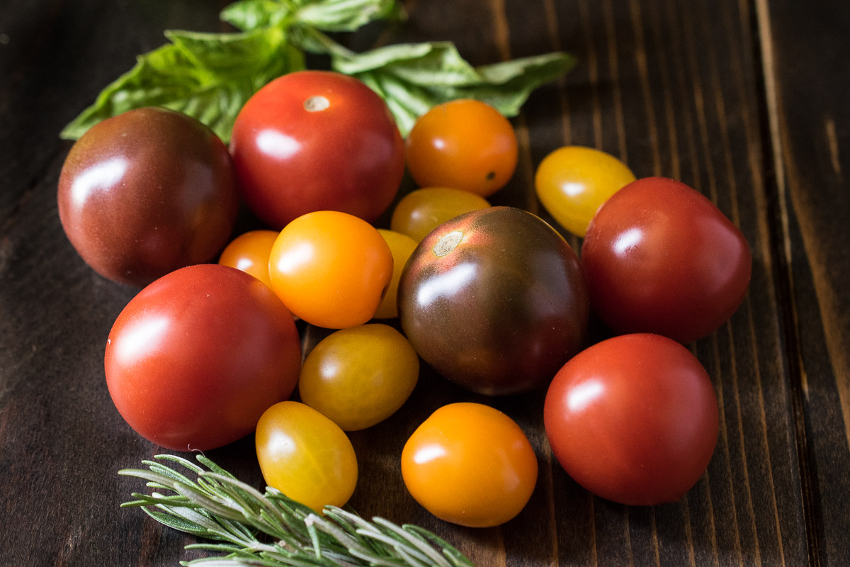 A collection of colorful tomatoes, basil and rosemary