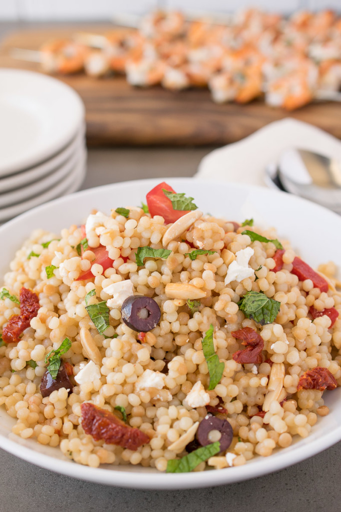 Mediterranean couscous salad served in a white bowl with olives, sun-dried tomatoes and basil