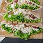 Tuna pita pockets lined up on a board
