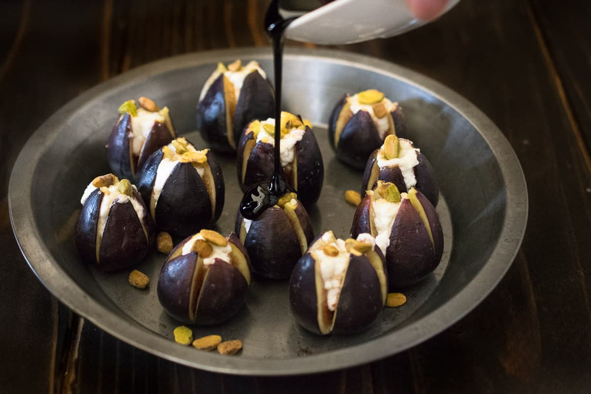 A plate of fresh figs cut open and filled with goat cheese and pistachios and balsamic glaze is drizzled over