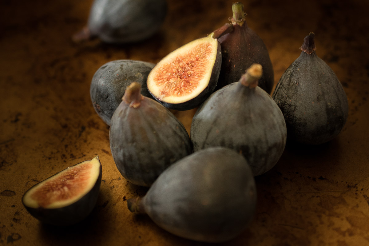 A selection of fresh figs with 1 sliced in half showing the delicious center