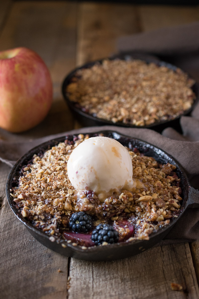 Apple and blackberry crumble in a small cast iron skillet topped with ice cream