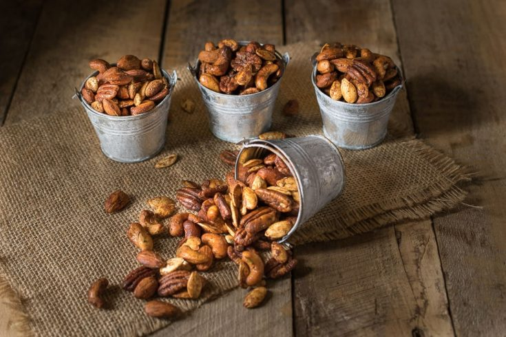 Mixed nuts roasted with spices and herbs presented in tin buckets