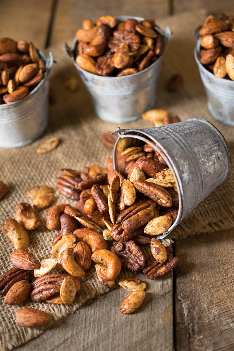 Autumn Spiced Nuts are presented in silver buckets with the one in front fallen over and the nuts spilling out