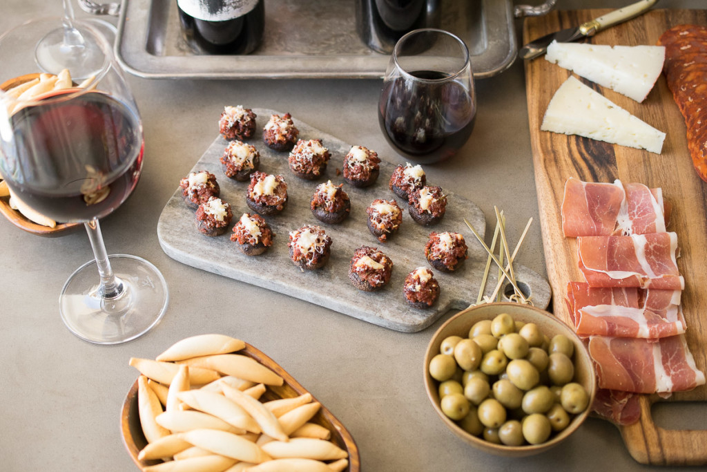 A table of tapas. Green olives, sliced meat, cheese and stuffed mushrooms