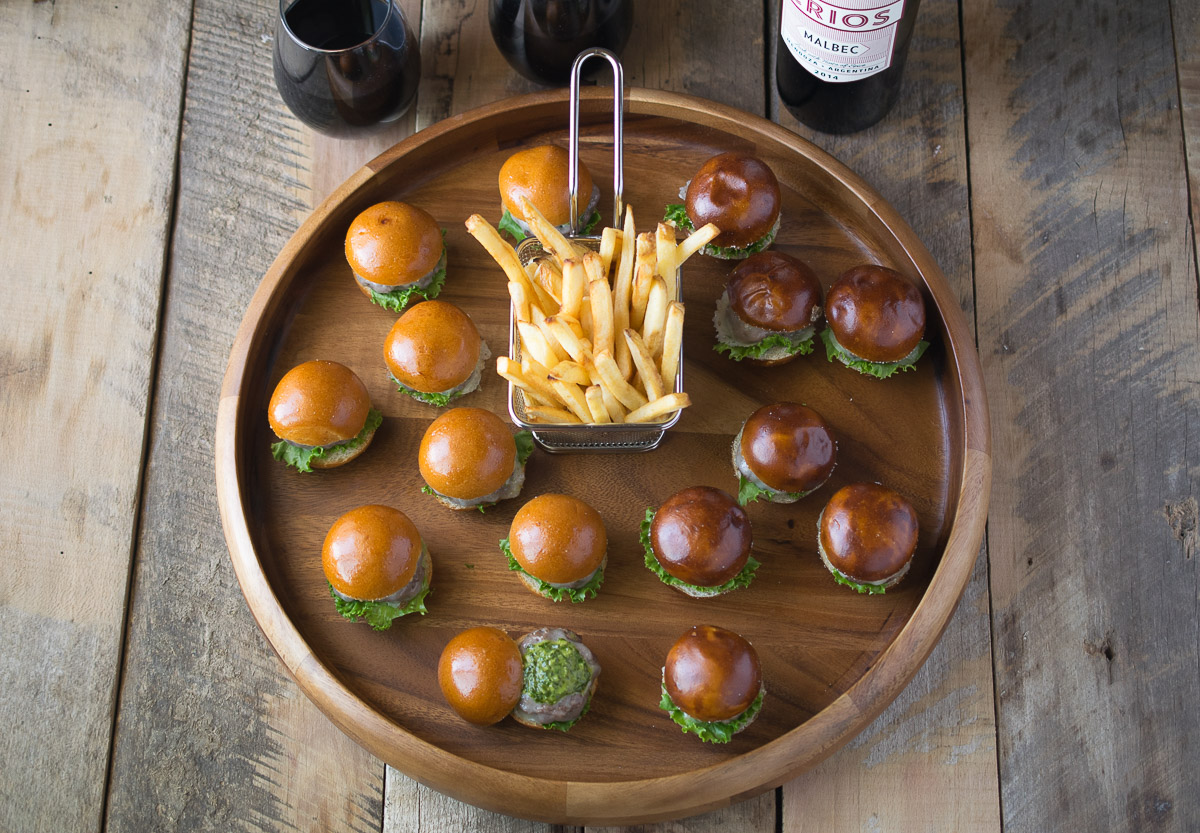 Chimichurri burger bites have chimichurri sauce in and on the burgers which are topped with melted provolone cheese and served on mini brioche and pretzel buns. These perfect 2-biters are paired deliciously with a fruity Argentine Crios Malbec wine.