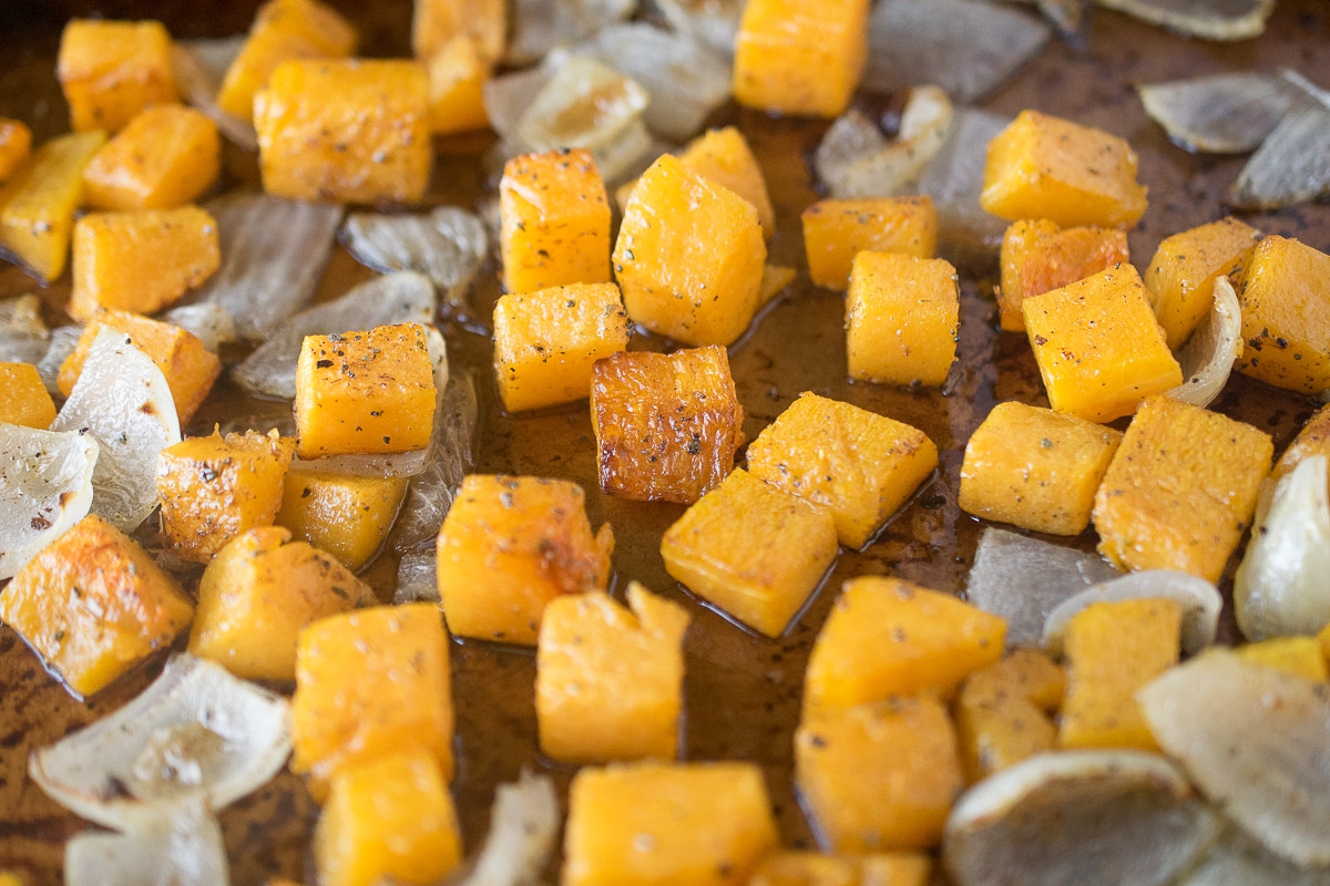 Roasted butternut squash and onion on a baking sheet
