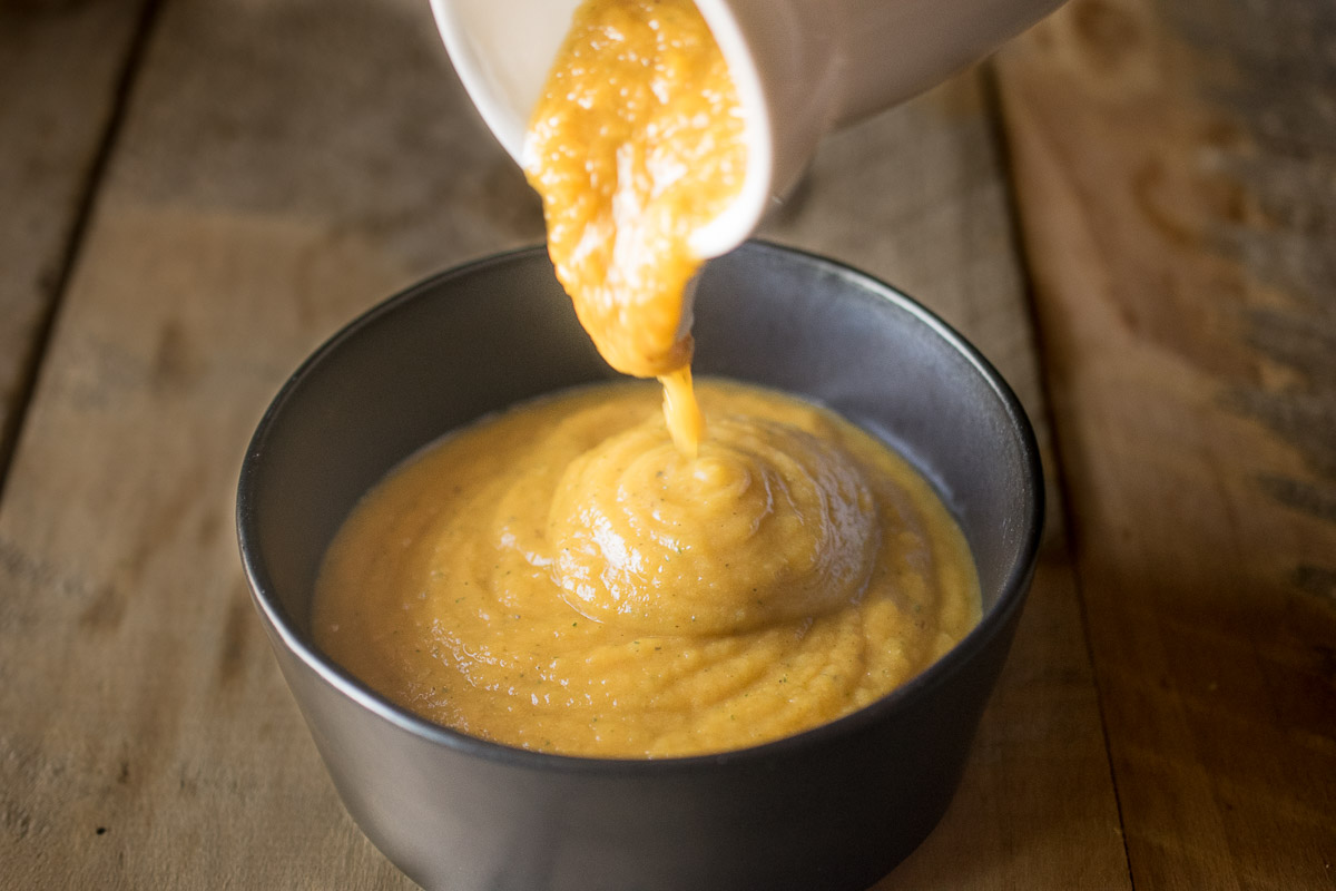 Orange butternut squash sauce being poured into a black bowl
