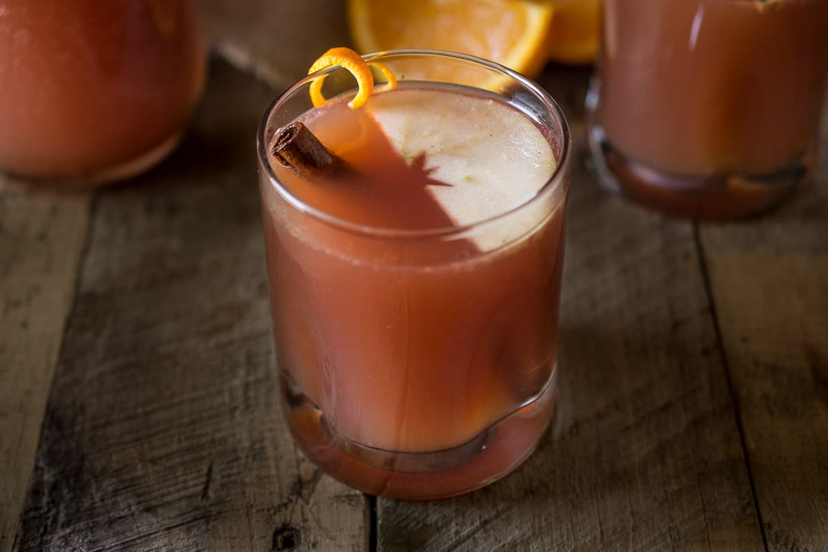 A glass of apple punch with a cinnamon stick, slice of apple and orange rind
